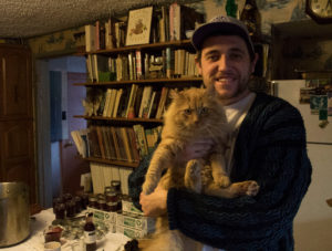 Owner and operator of The Barking Kettle is holding his cat, Douglas, who helps him forage food.