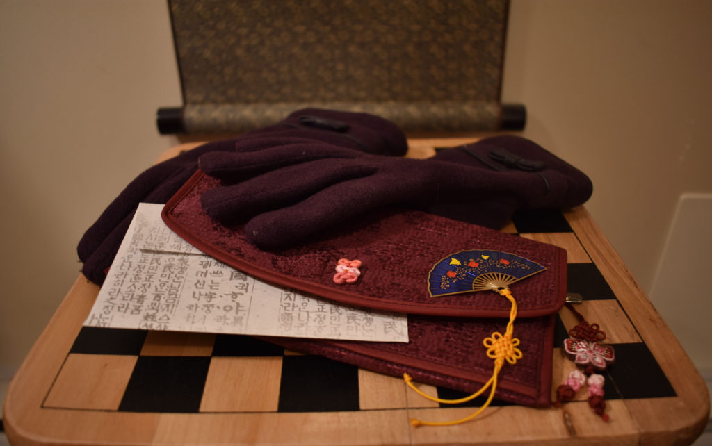 South Korean gloves, wallet, bookmark, and envelop rest on a chessboard.