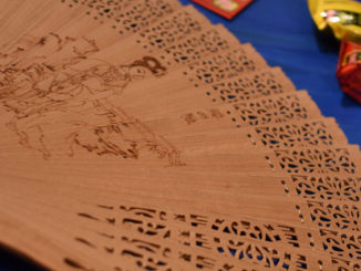 A Chinese wooden fan, candy and red envelopes.