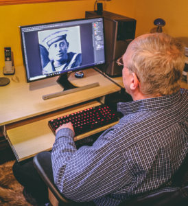 Gerard Nash restoring a photo of a Navy officer in his home in St. John's.