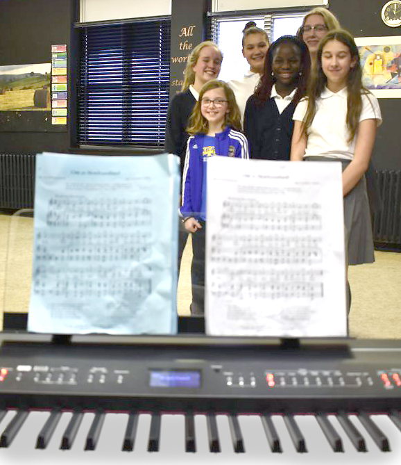 Angela Warren's music students pose before the piano for a photograph after their interviews.