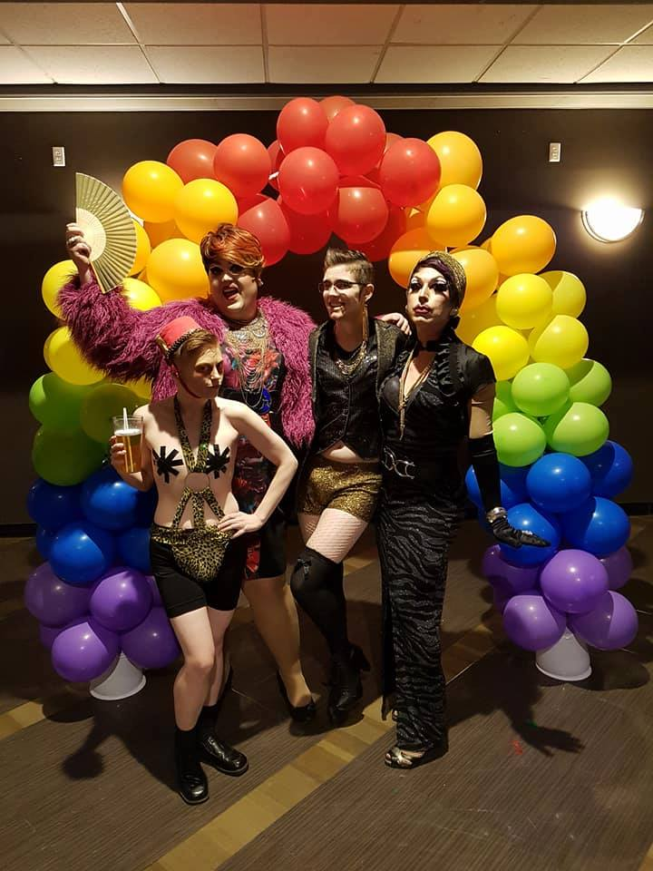 Drag performers from pose under the balloon umbrella at Queer Prom. From left to right, Johnny Diamond, Evelyn J Tudor, Dr. Androbox, and Fashionista Jones.