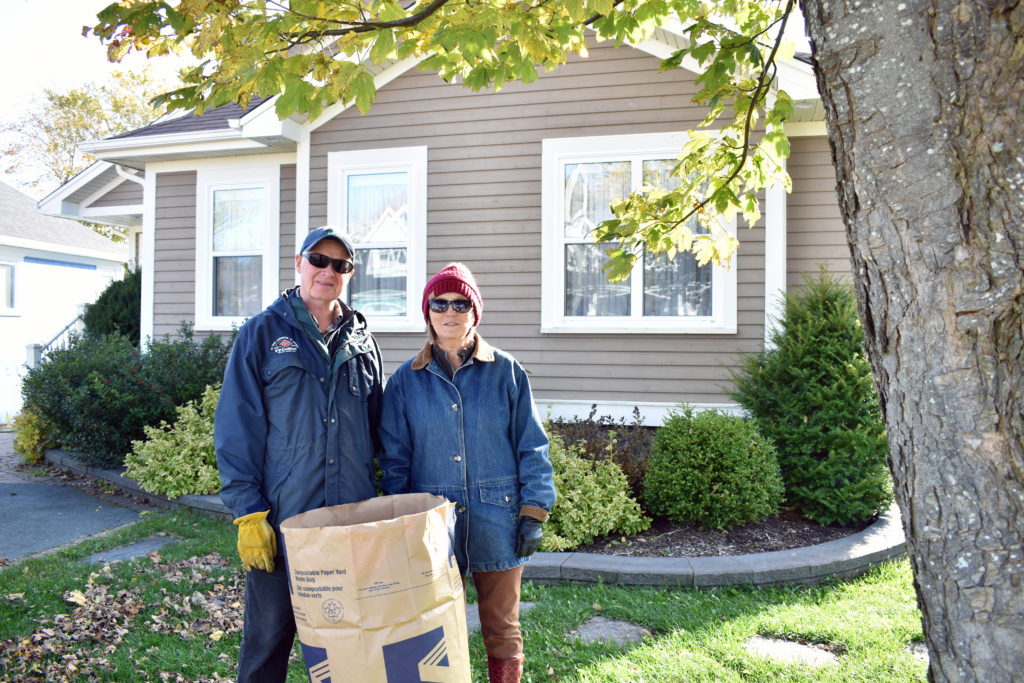 A couple standing in their front yard with a large bag of leaves on a Fall day in St. John's.