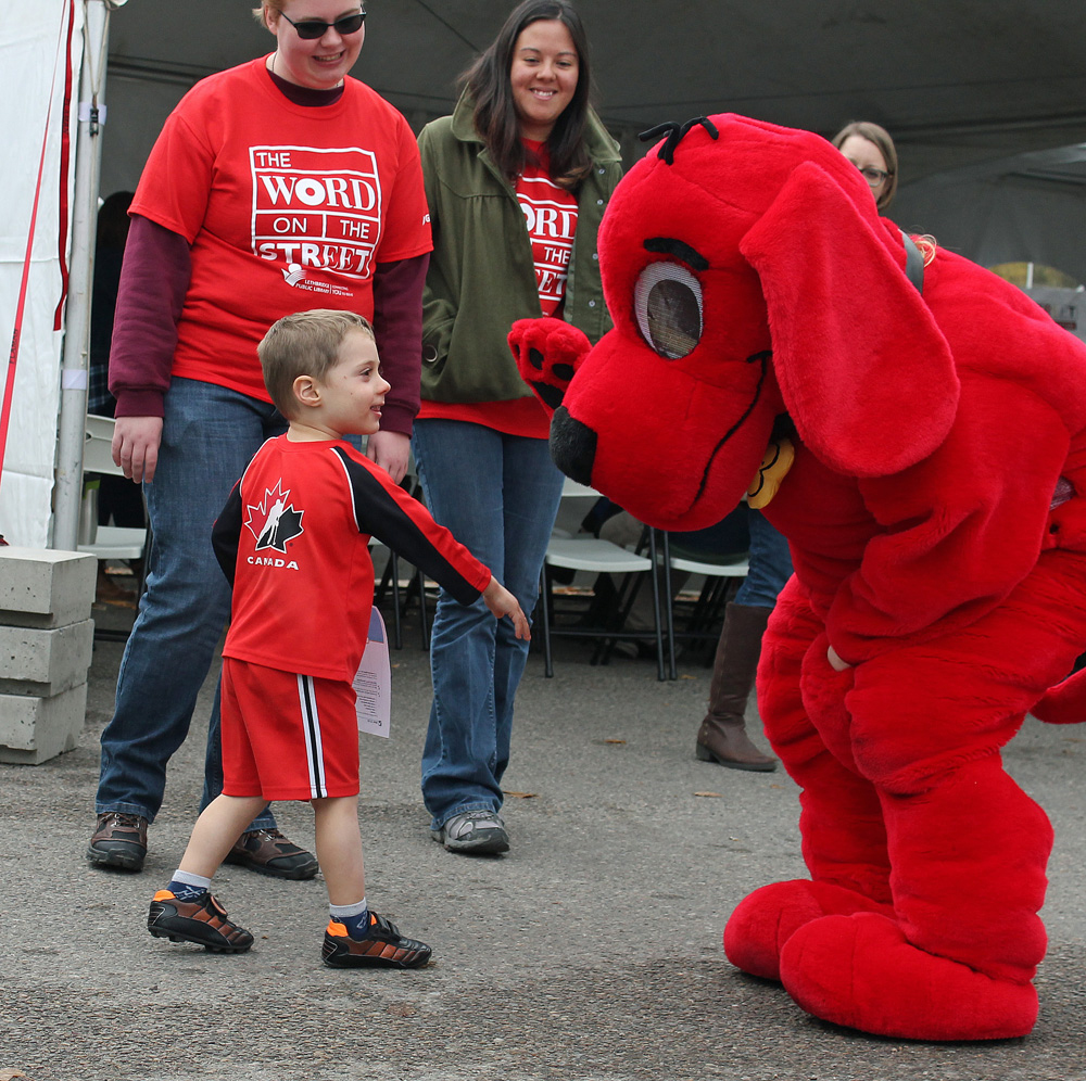 Cormac Fairweather gives Clifford the Big Red Dog a high five uring the Word on the Street Festival in Lethbridge, Alberta.