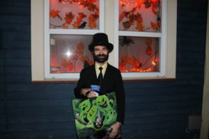 Man holding halloween bag in front of decorations.