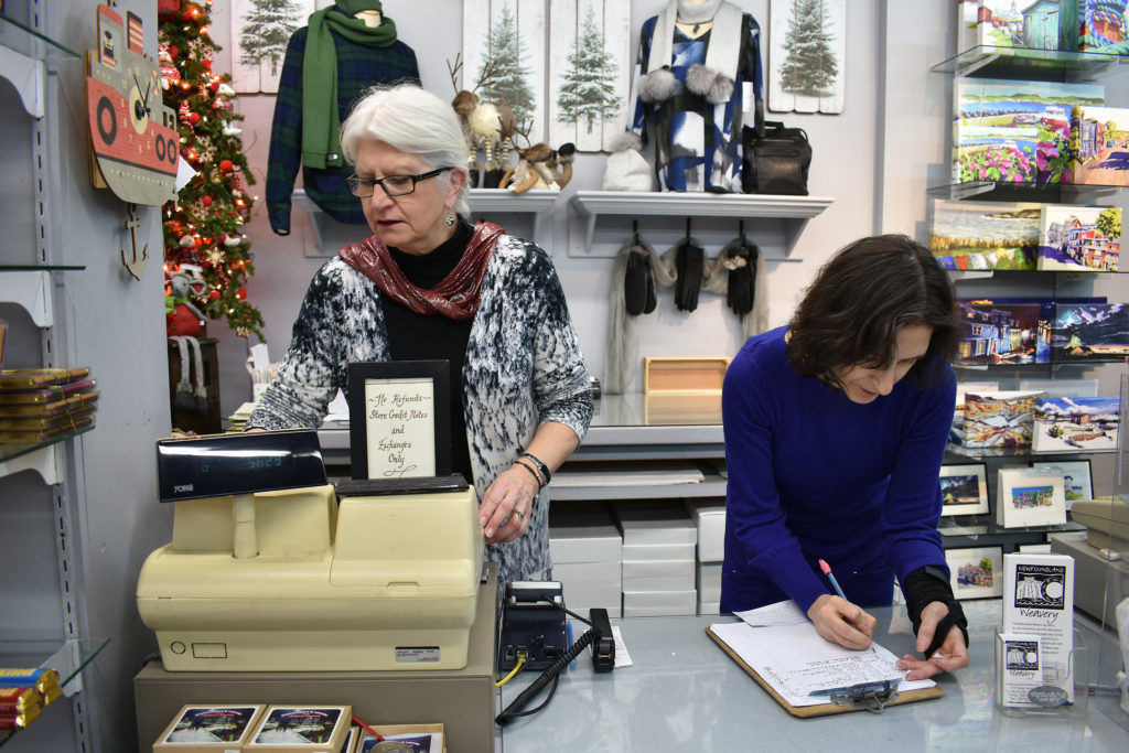 two women are standing at a store counter.