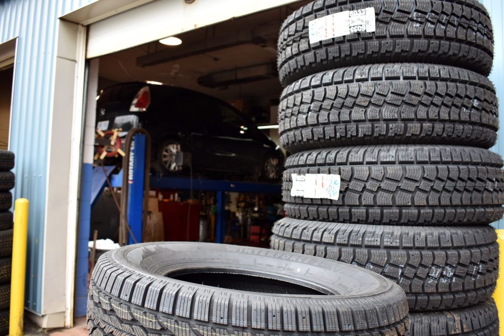 A pile of tires is in the forefront of an auto service station. In the background a car is up on a ramp having its tires installed for winter.