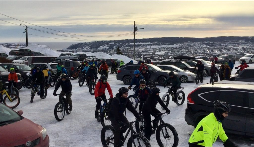 The 2019 Pippy Snowbike Festival's bikers prepare to leave the Admirals Green Golf Course Club House's parking lot. The bikers steer their fat bikes toward the freshly groomed bike course through the snow.