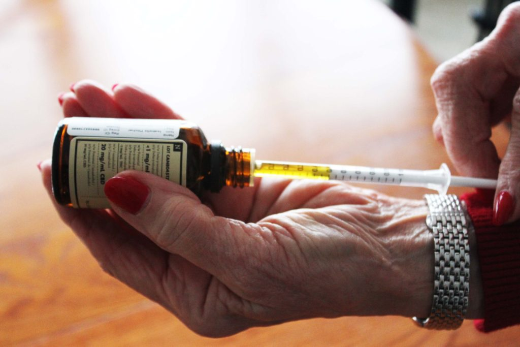 Mickie Pitcher, 77, of St. John's draws her regular dose of CBD oil with a syringe. Pitcher began taking CBD oil last year after experiencing the frightening symptoms of opiate withdrawal. Many seniors are turning to cannabis as a safer alternative to medications that include opiates.