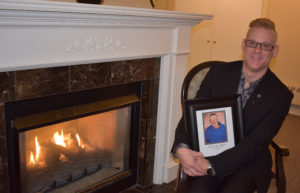 Hubert Locke's nephew, Grant Janes-Locke, holds a photograph of his uncle. Janes-Locke is a funeral director who will be directing at his uncle's funeral.