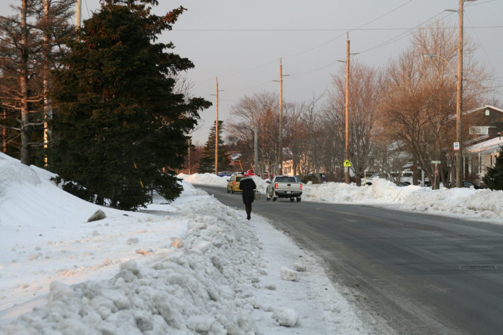 A woman walking on a skinny, uncleared sidewalk beside a busy cleared street.