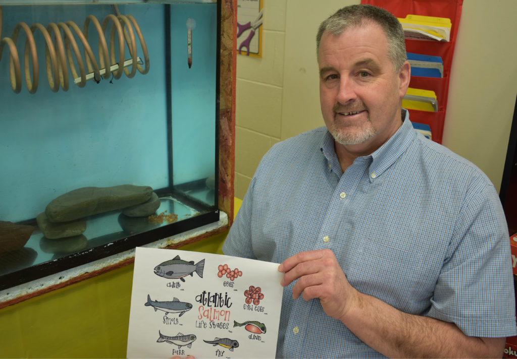 David Sullivan, a Roncalli Elementary grade four teacher, explains the life cycle of Atlantic salmon life stages. In the background, the salmon eggs are hatching.