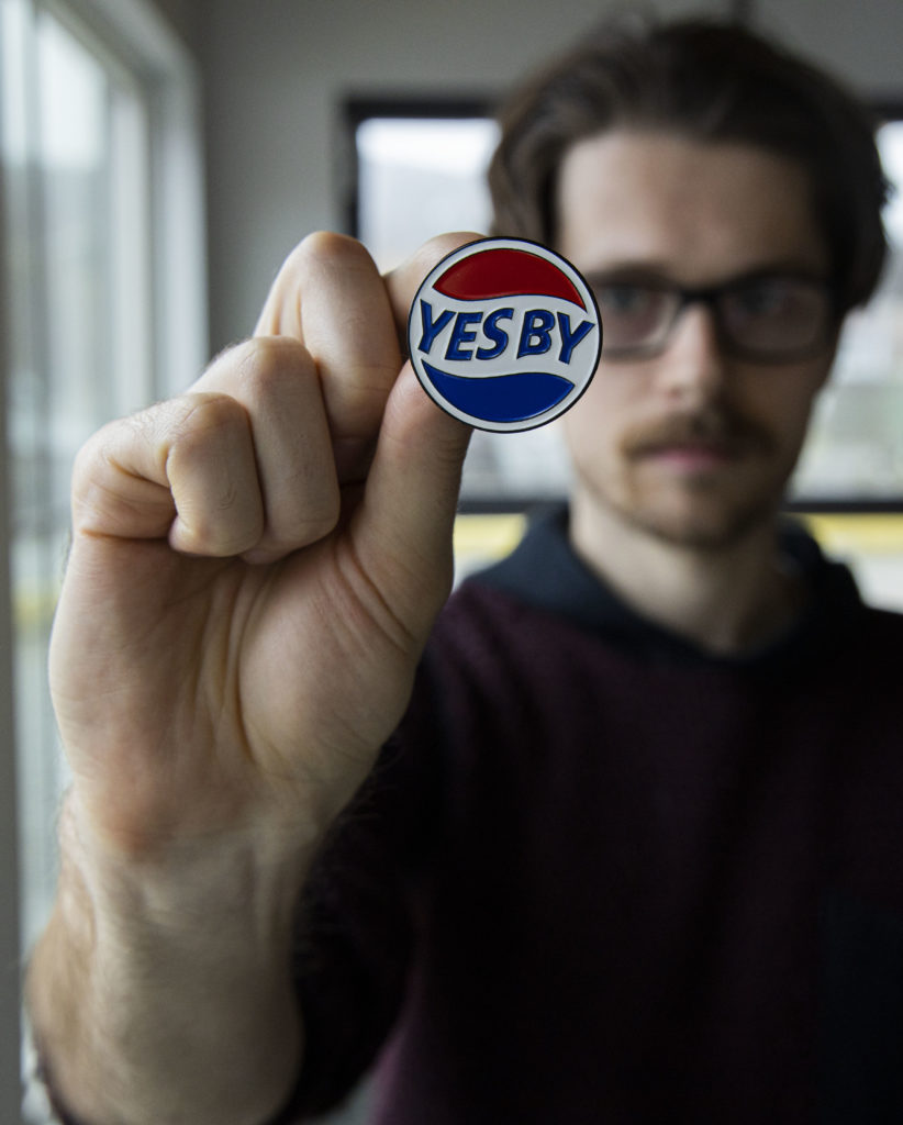 "Etsy shop owner Alex Wilkie holds up an enamel pin that says ""Yes By."""