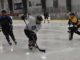 a player skating into the corner with the puck as three opponents chase him down to get the puck at the Paradise Double Ice Complex
