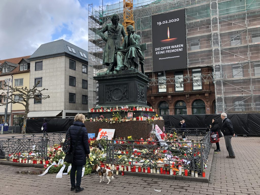 "People stand around an impromptu memorial for the victims of the Hanau shooting. Wreaths and candles have been laid down around the sculpture of Brothers Grimm on the marketplace. A banner on town hall reads ""The victims weren't strangers. #hanaustandstogether"". Photo courtesy of Hessischer Rundfunk"