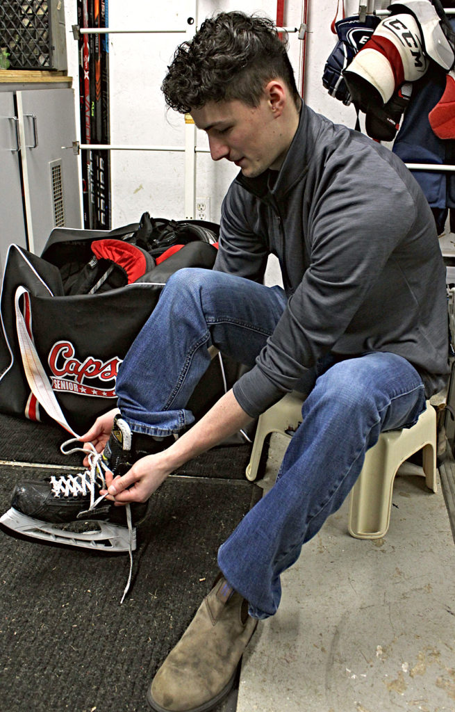 St. John's Caps player Colin O'Neill laces up his hockey skates.