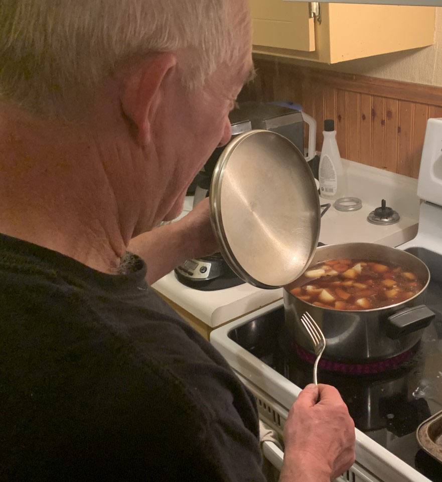 Rick Dunne tends to the stove as a pot of moose stew cooks. Dunne got the moose on Monday.