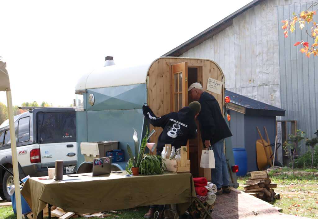 Evan Brown, carpenter and artist, shows customer the sauna he built from an old horse trailer.
