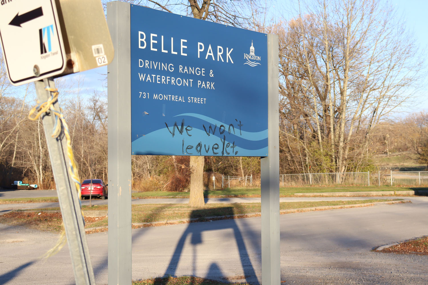 """Image of Belle Park where people experiencing homelessness lived in the summer. The words """"we won't leave yet"""" has been written on the sign."""