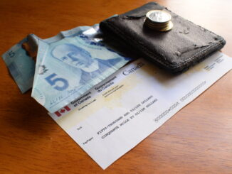 a cheque sits next to some money in this photo illustration