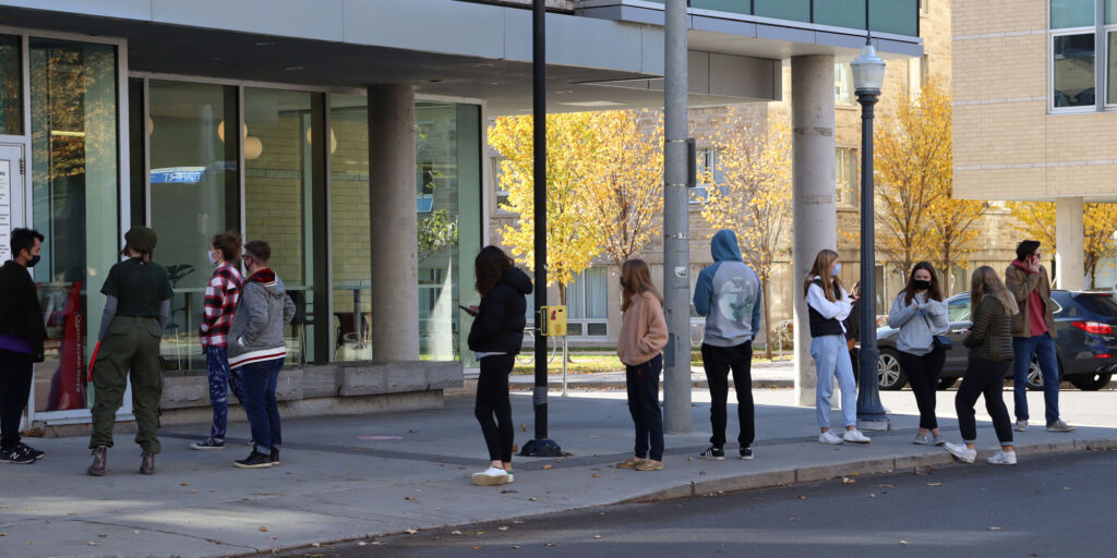 Photo depicts a group of Queen's students waiting in line to get lunch on Saturday Oct. 31st.