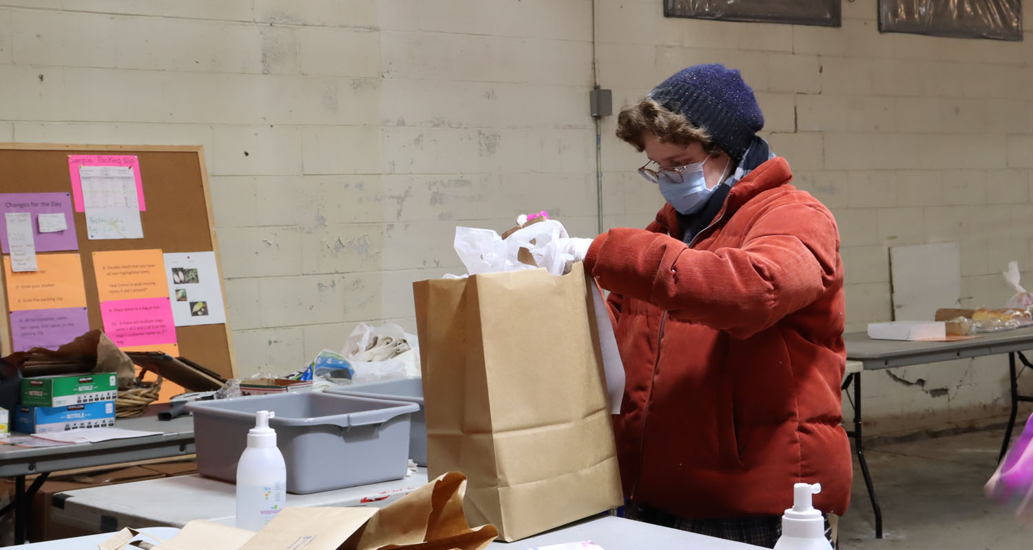 Photo of person working at the farmer's market pick up location. Individual is filling paper bag with food