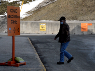 A man crosses the street towards the Corner Brook vaccination clinic.
