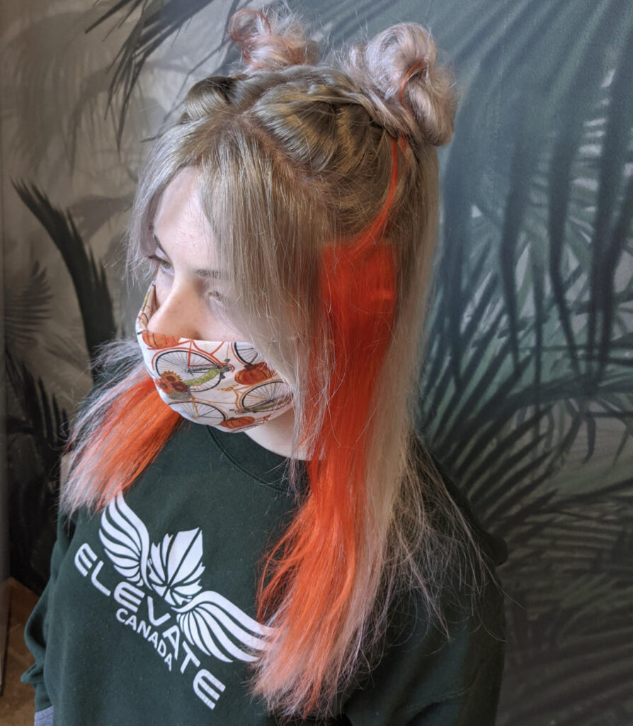 A client of hairstylist Emma Whitt poses while wearing a face mask.