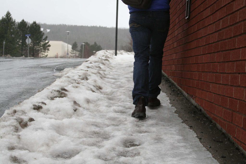 Man walks on icy sidewalk.
