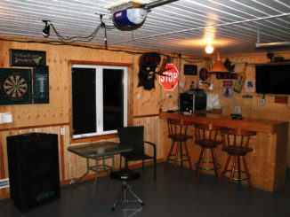 Wooden shed with signs on the wall. Bar and bar stools set up.
