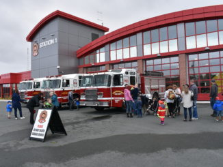 Parents and children standing in a line up by three fire trucks outside of a fire station