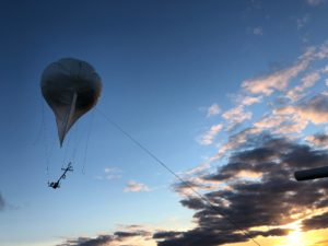 Weather balloon in dusk sky.