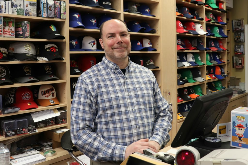 Maverick Sports and Collectables. Man Standing at counter