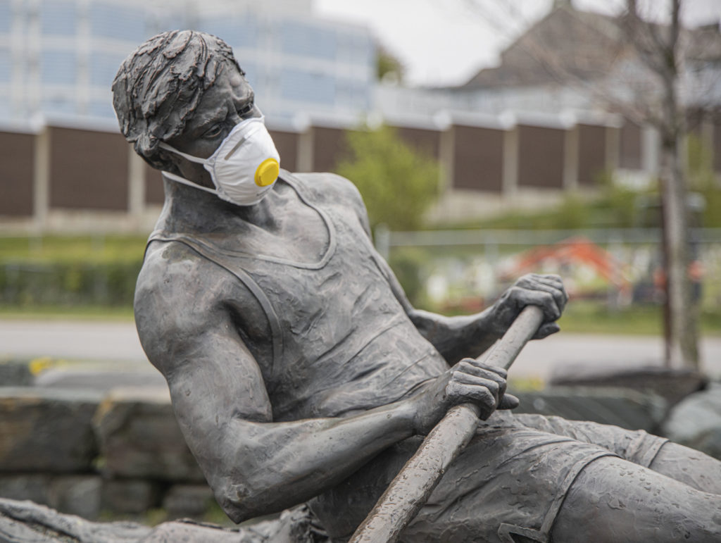 A photo illustration of a sculpture of a rowing crew member wearing a medical mask.