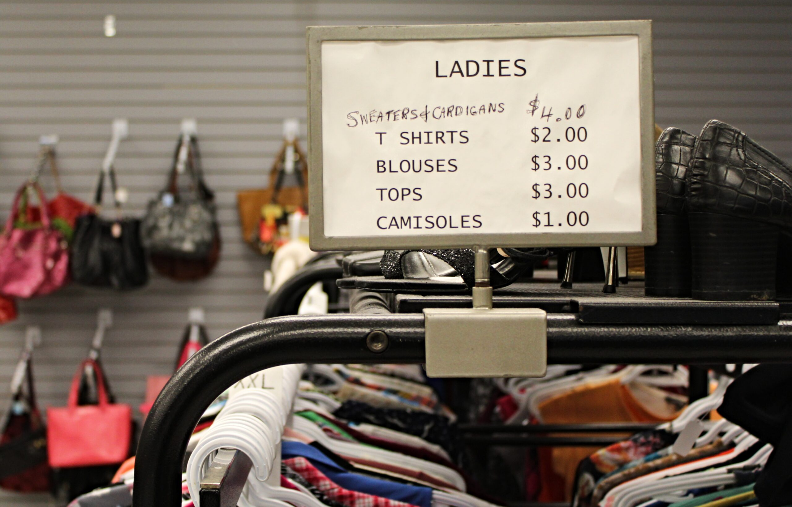 Signage at thrift store shows shirts priced as low as $1