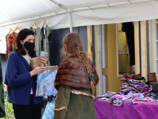 The main organizer of the market helping a customer