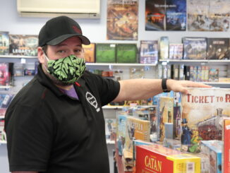 Dan Morton, manager at Midgard gaming, standing next to a row of board game boxes.