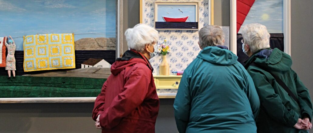 A group of elderly women gather at Nan's House exhibit to look at the artwork. The piece they're observing is titled 'Wild flowers.'