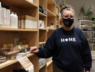 """White woman with grey hair and blue shirt that says """"home"""" stands next to a shelf of soap in a store."""
