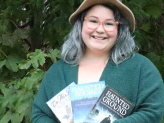 Ashley DeMoss stands with her collection of ghost tale books by Dale Jarvis, founder of the Haunted Hike.